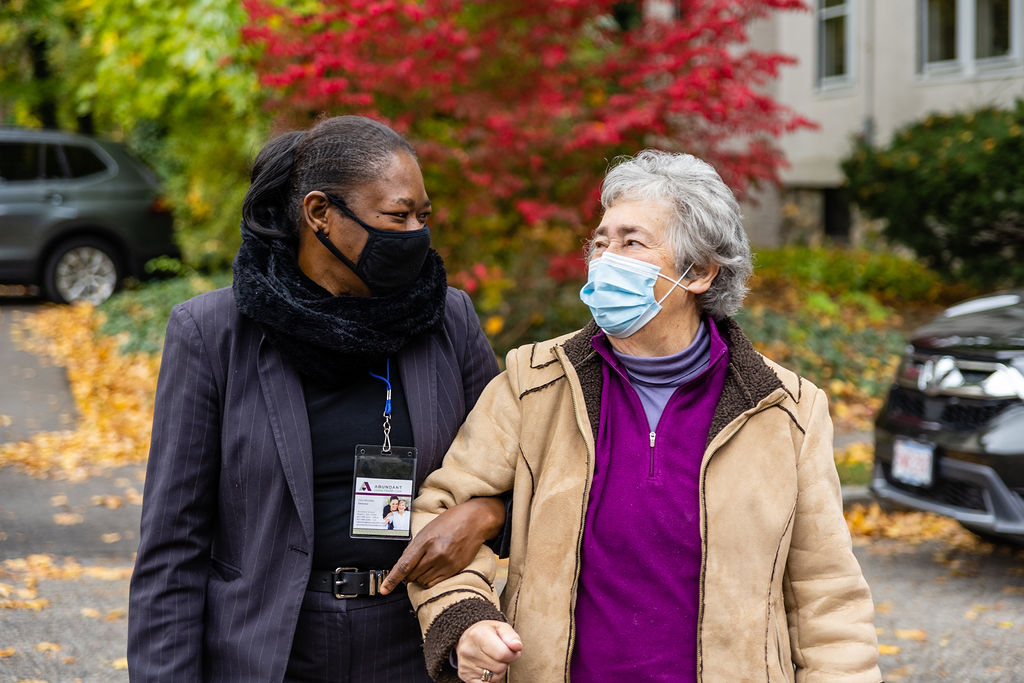 Abundant Home Health Care aide assists her patient. They are smiling at each other underneath their face masks. 24-hr in-home care.